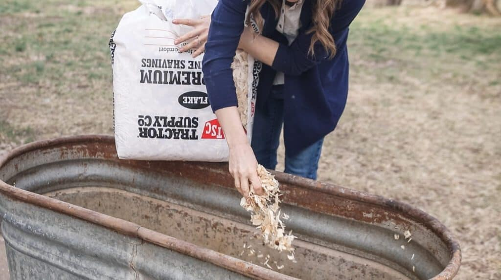 women adding Tractor Supply pine bedding into chicken coop