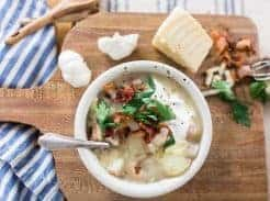 healthy potato sop in a white bowl topped with fresh herbs and bacon. Bowl of soup is on a wood cutting board topped with fresh ingredients and next to a blue and white stripped towel