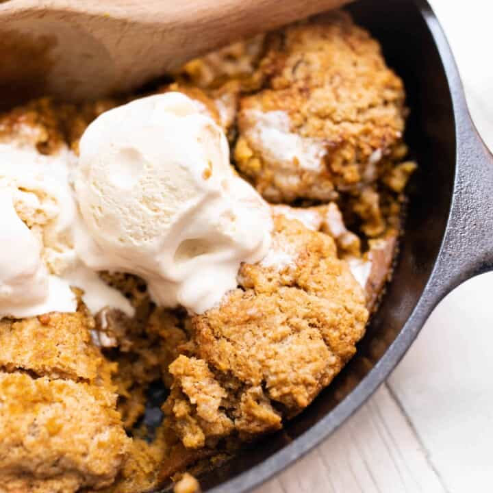 sourdough pumpkin cobbler topped with ice cream in a cast iron skillet with a wooden spoon scooping out a serving