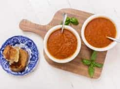 two bowls of roasted red pepper and tomato soup on a wood cutting board with basil. Grilled cheese on a blue and white plate is to the left
