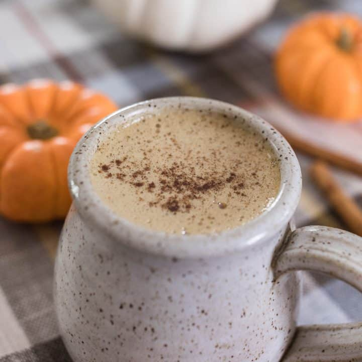 bulletproof pumpkin spice latte topped with pumpkin spice in a stoneware mug with pumpkins behind it