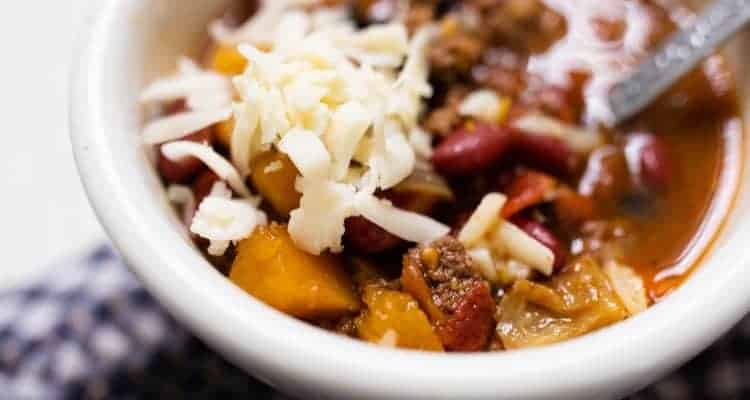 white bowl full of pumpkin chili with ground beef and topped with cheese