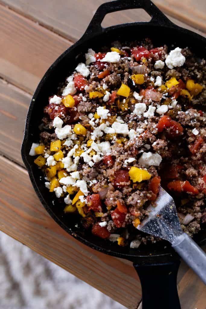 cast iron skillet with ground beef, quinoa, pumpkin, feta cheese, garlic and onions to make stuffed peppers