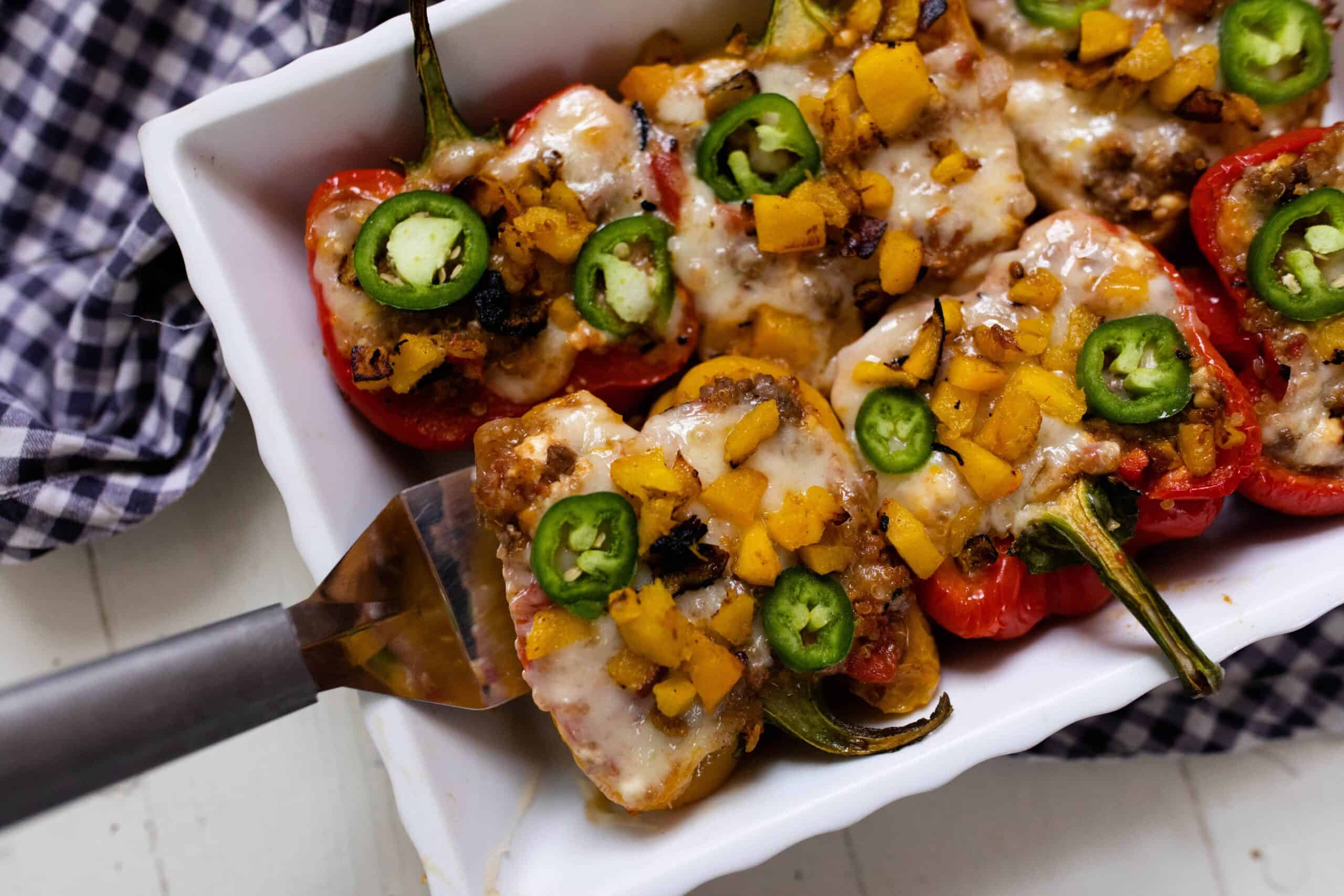 baking dish full of stuffed bell peppers with ground beef, covered in melted cheese and topped with sliced jalapenos.