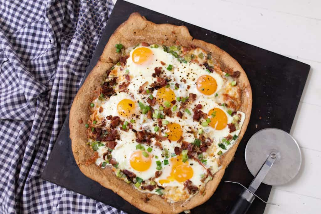 breakfast pizza loaded with eggs, bacon, tomatoes and olive on a black stone on top a white and blue towel