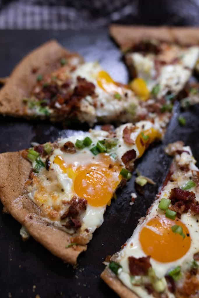 slices of breakfast pizza topped with bacon and eggs