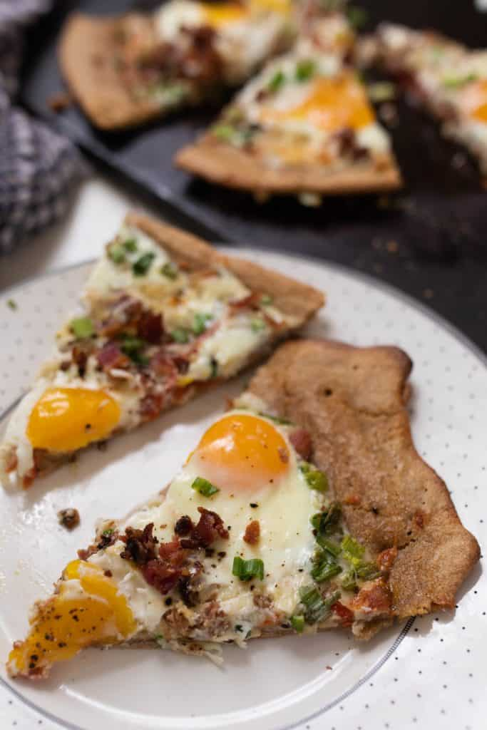 two slices of sourdough breakfast pizza topped with cheese, bacon, eggs, and green onions on a white place