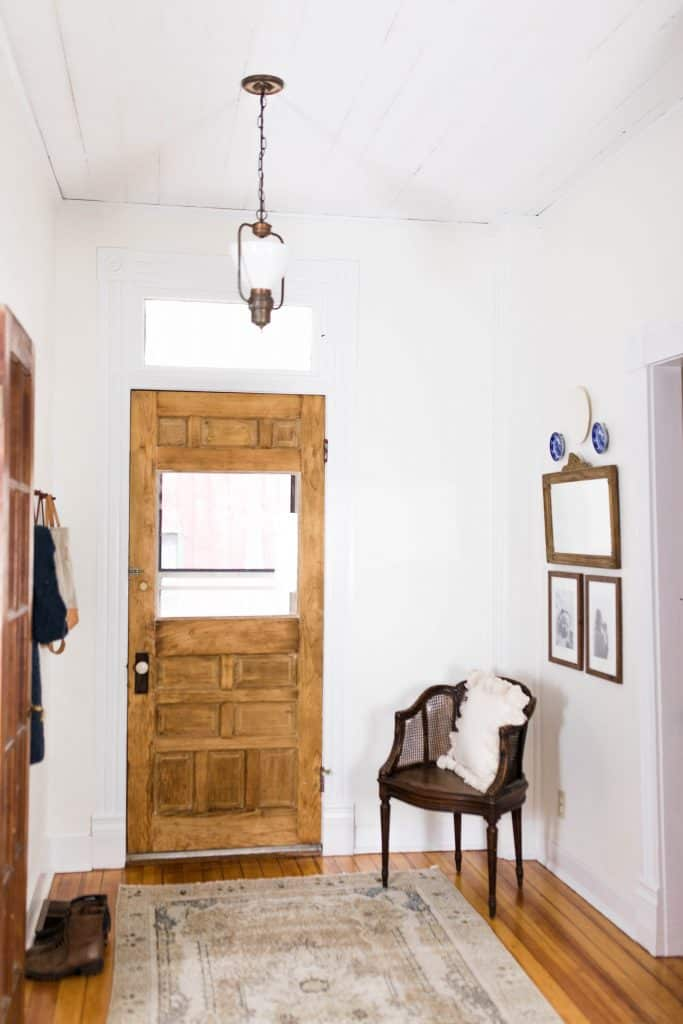 Victorian farmhouse entryway with original wood door, wood chair with white tassel pillow and a vintage mirror to the right.