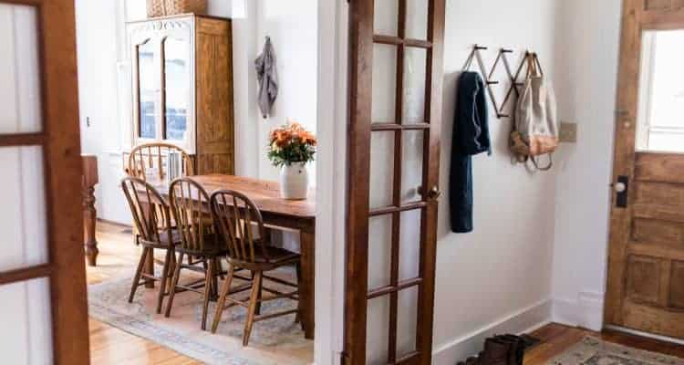 French doors to the eat-in kitchen are opened and showing gorgeous antique furniture