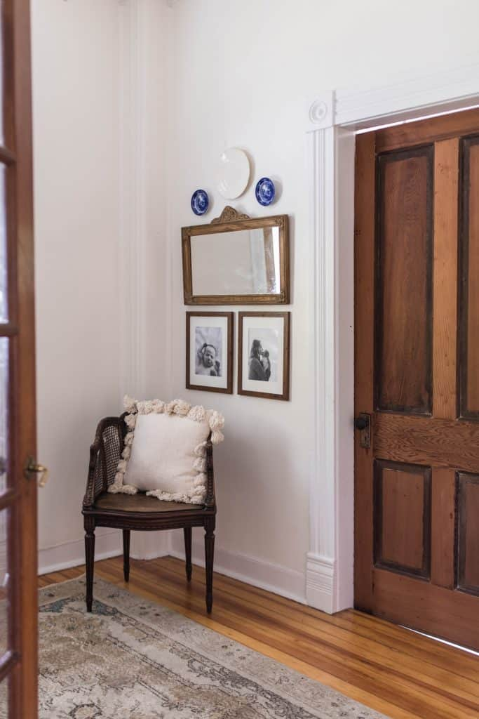 antique mirror with two family pictures hanging below it with a antique chair beside it