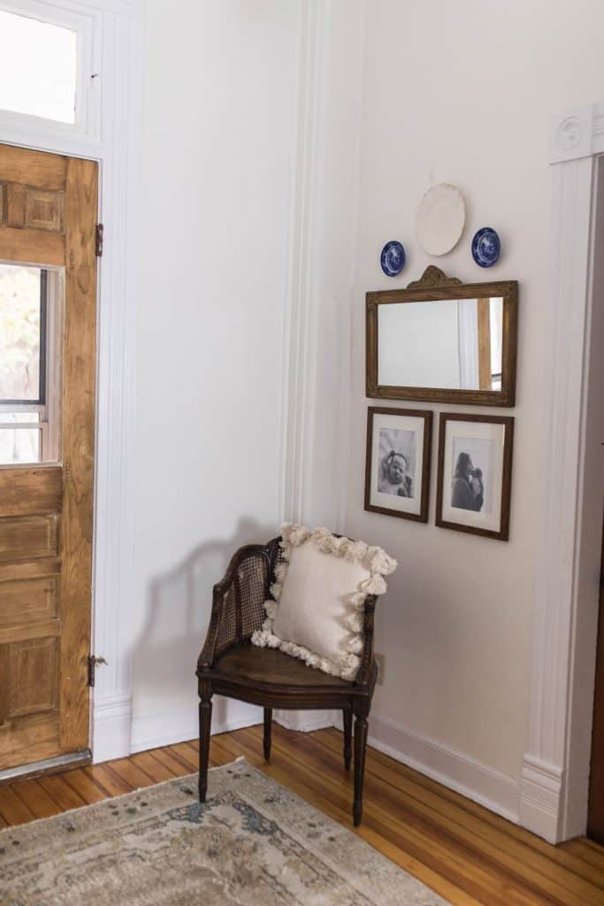 Antique wood chair with cream colored tassel pillow. On the wall hangs one white and two blue plates, an antique wood rectangular mirror, and two pictures in a wood frames underneath the mirror