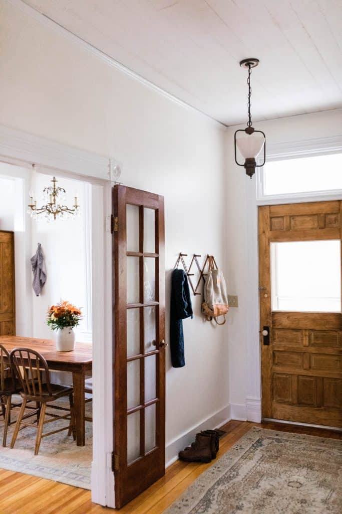Farmhouse entryway with wood French door, Turkish rug, and antique hat rack