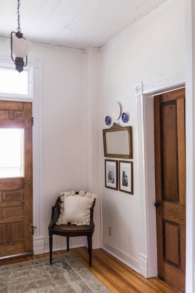 farmhouse entryway - two doors stripped down to the original stain color. Antique lighting hangs above and a chair with wall decor sits in the corner