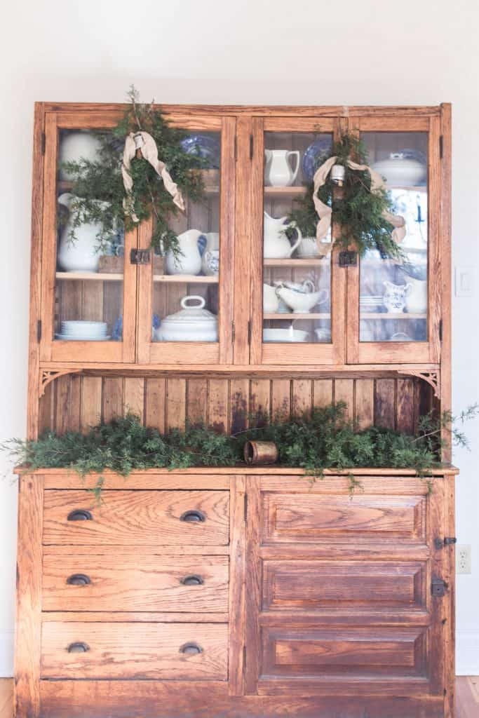 Antique hutch topped with fresh greenery, bells, and candles. Two