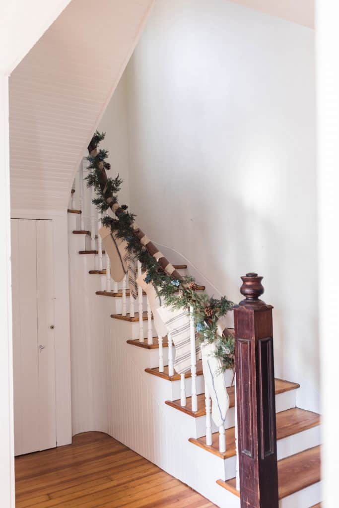 Antique farmhouse stairs wrapped in greenery and stocking hung for a farmhouse Christmas tour