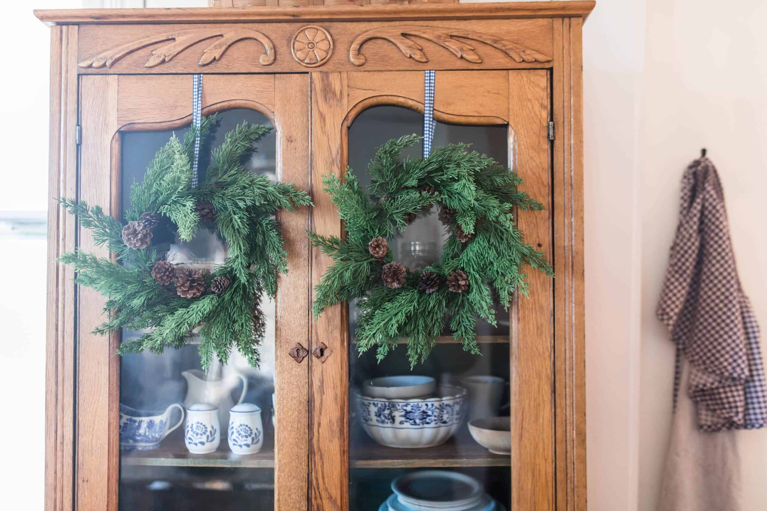 greenery wreaths hung with ribbon on an antique hutch for farmhouse Christmas tour