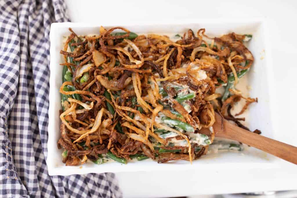 homemade classic green bean casserole from scratch topped with fried onions. A wooden spoon is in the dish.