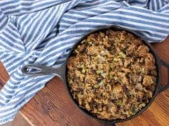 homemade sourdough stuffing with celery and onion in a cast iron skillet on top a wood counter-top with a blue and white striped towel