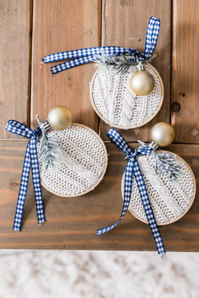 3 handmade Christmas ornaments made from a thrifted sweater in embroidery hoops and topped with ribbon, faux greenery, and blue and white ribbon on a wooden table