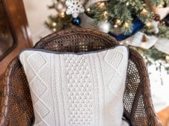 pillow made from a white sweater with blue piping on a wood chair with a Christmas tree in the background