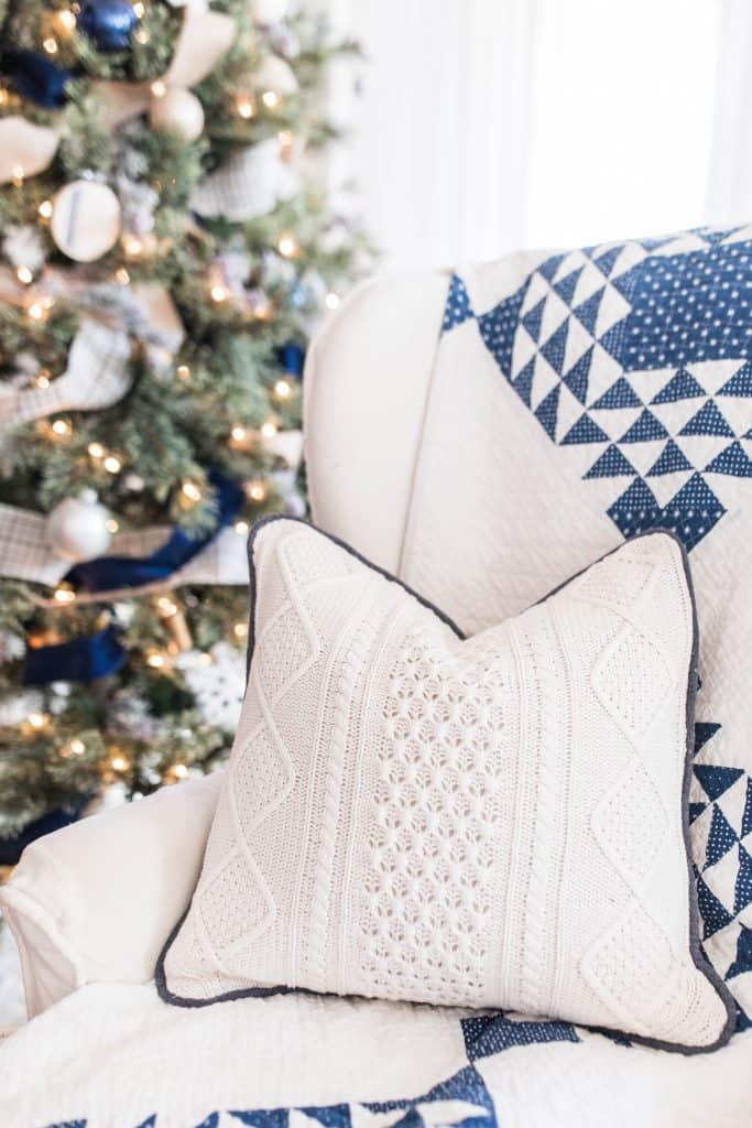 sweater pillow with blue cording on a white wing-back chair with a blue and white quilt draped over the back.