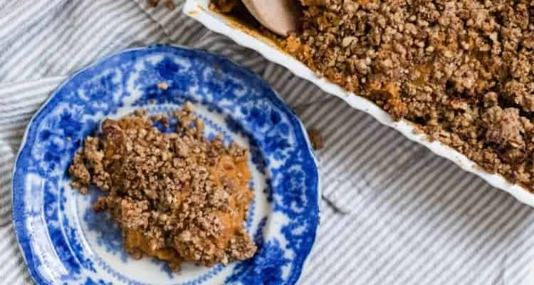 healthy sweet potato casserole recipe with pecan topping on a blue and white antique plate and a baking dish with the remaining sweet potato casserole in a baking dish behind
