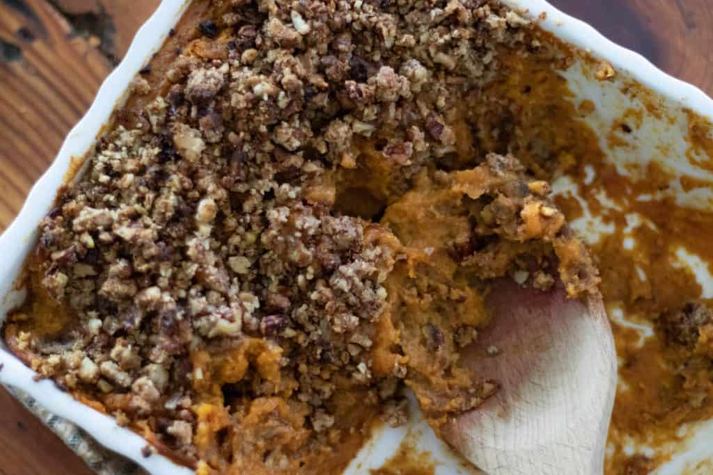 white baking dish of sweet potato casserole with pecans with a wooden spoon serving some up