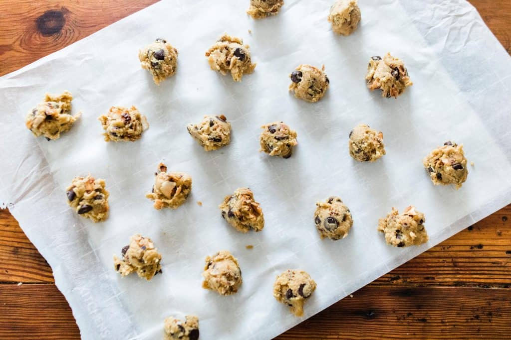 even scoops of cookie dough on a parchment lined cookie sheet
