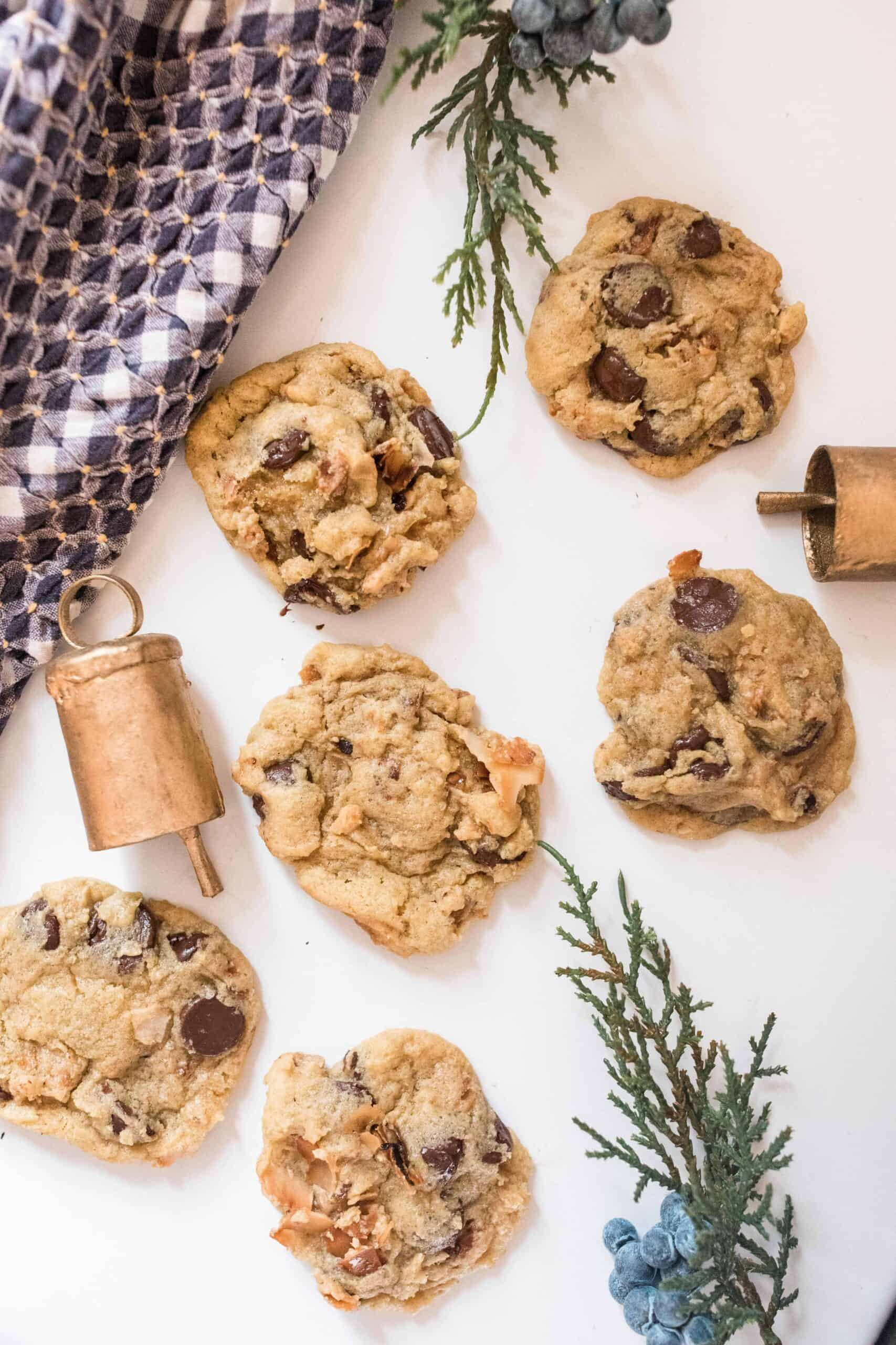 toasted coconut cookies on a white countertop with bells and greenery spread out around the cookies