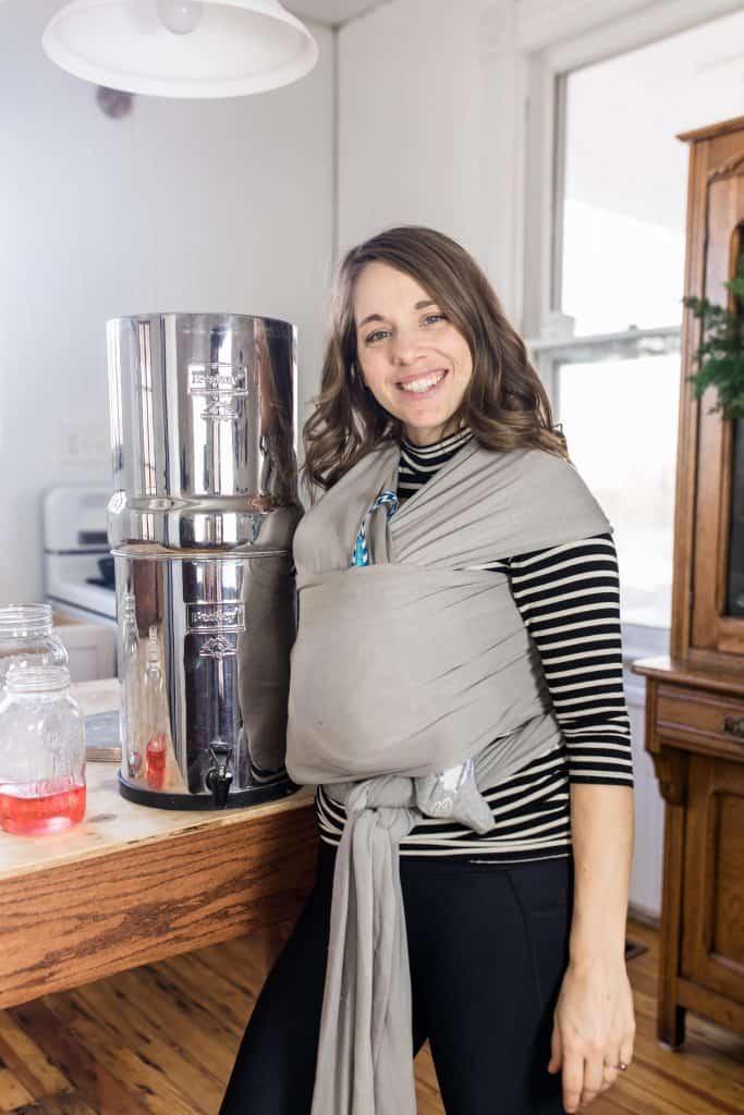 women wearing a baby standing next to a Berkey Water filter smiling