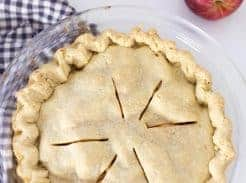 homemade apple pie in a glass pie dish on top antique stove with a blue and white checked towel under the pie and two apples in the back