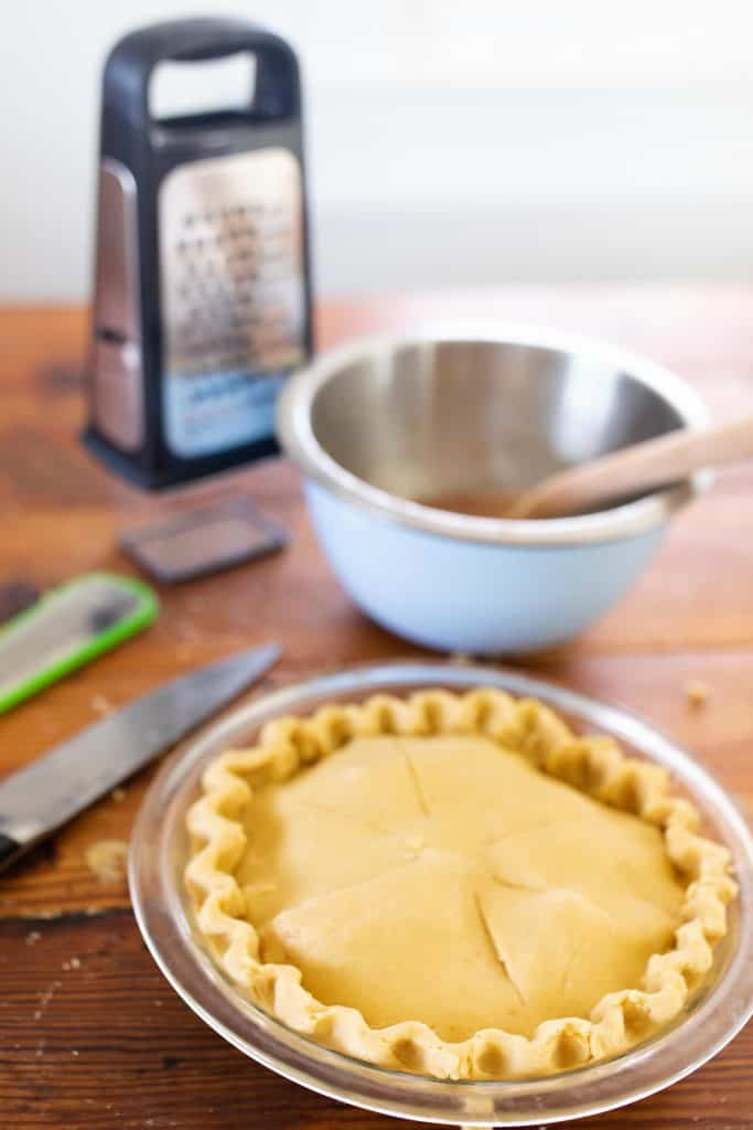 einkorn apple pie in a glass dish with bowl and cheese grater behind