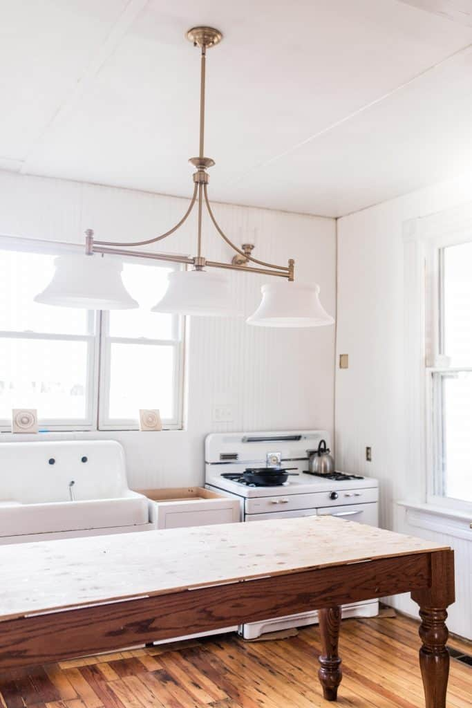 victorian farmhouse kitchen update with new white cabinets, antique sink and stove, and a handmade island. New brass lighting hands over the island