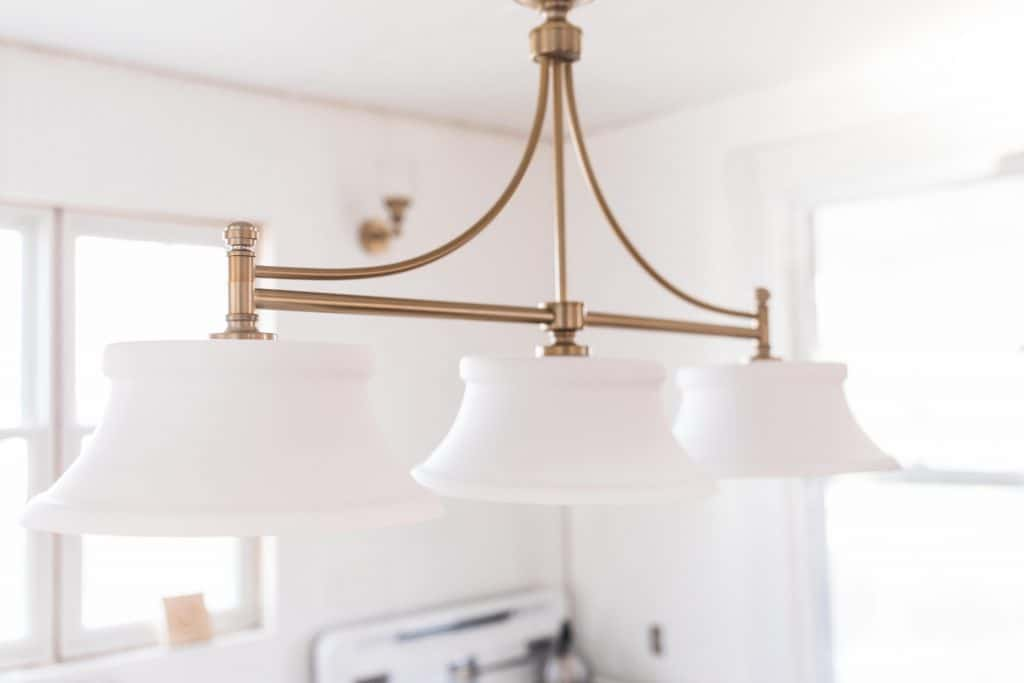 beautiful brass light fixture with three glass lamps in a victorian farmhouse