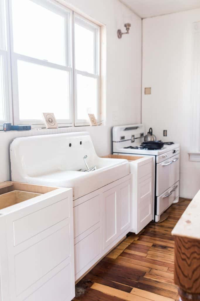 new white base cabinets, with a antique sink and custom cabinets below