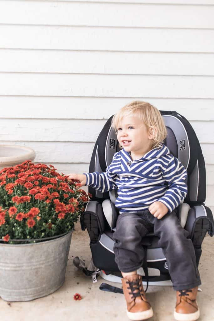 toddler boy smiling white sitting in a carseat on his front porch next to flowers.