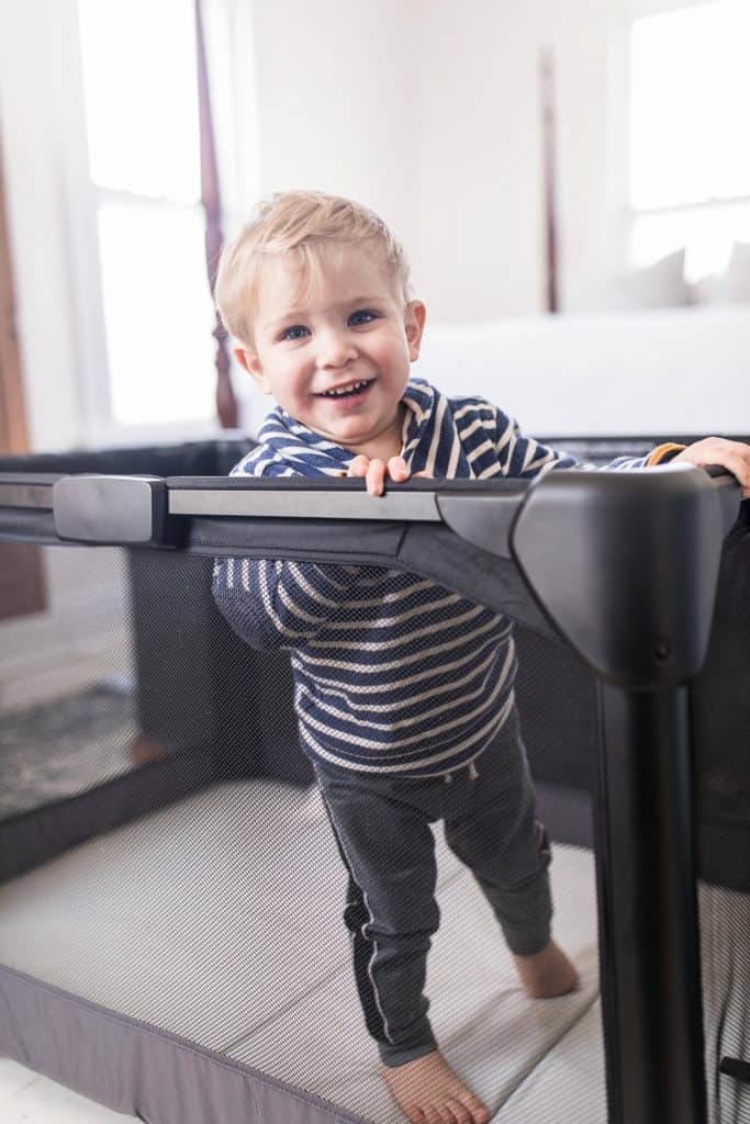 toddler standing in a travel crib next to a bed.