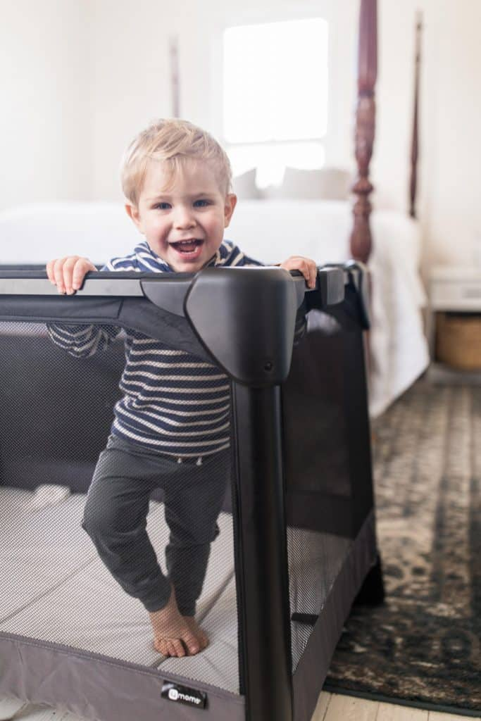 toddler wearing a blue and white stripped shirt standing I a travel crib in a bedroom