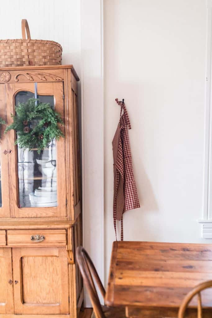 diy reversible apron hanging on a hook next to a wood China cabinet