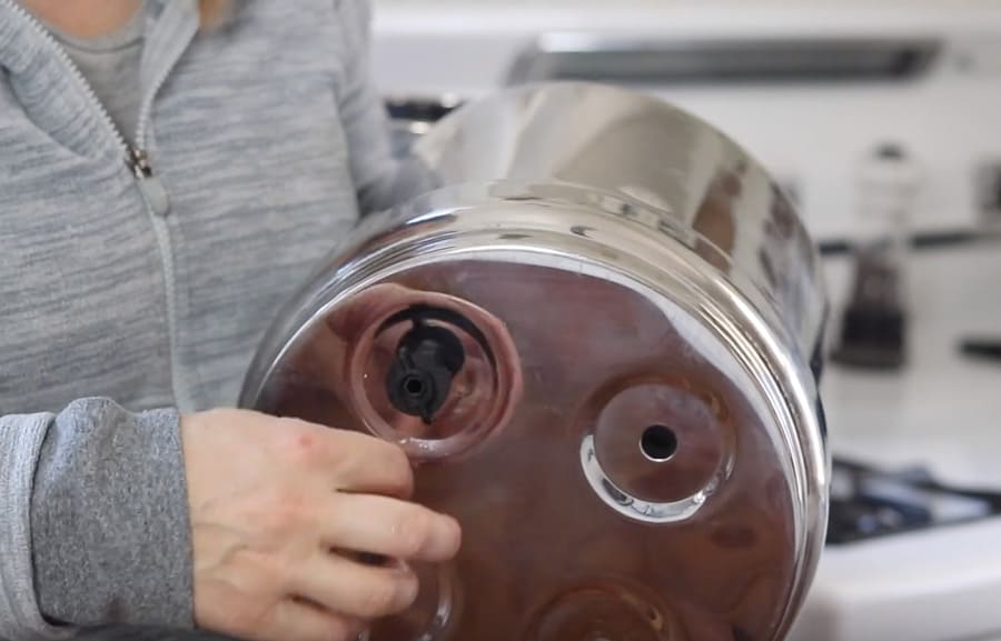 screwing on the plastic nut to the bottom of the top chamber of the Berkey water filter