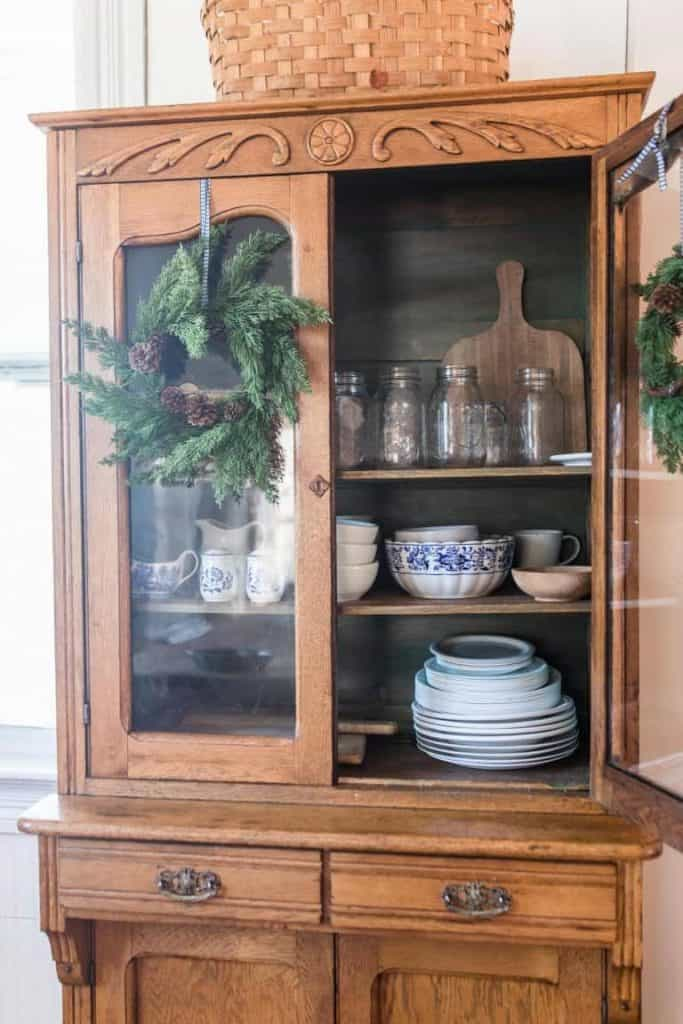 large wood China hutch with the door open showing dishes and mason jar glasses
