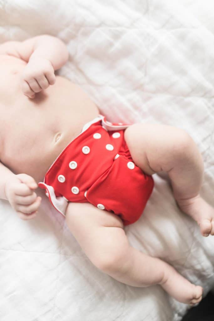 two month old baby wearing a red newborn cloth diaper