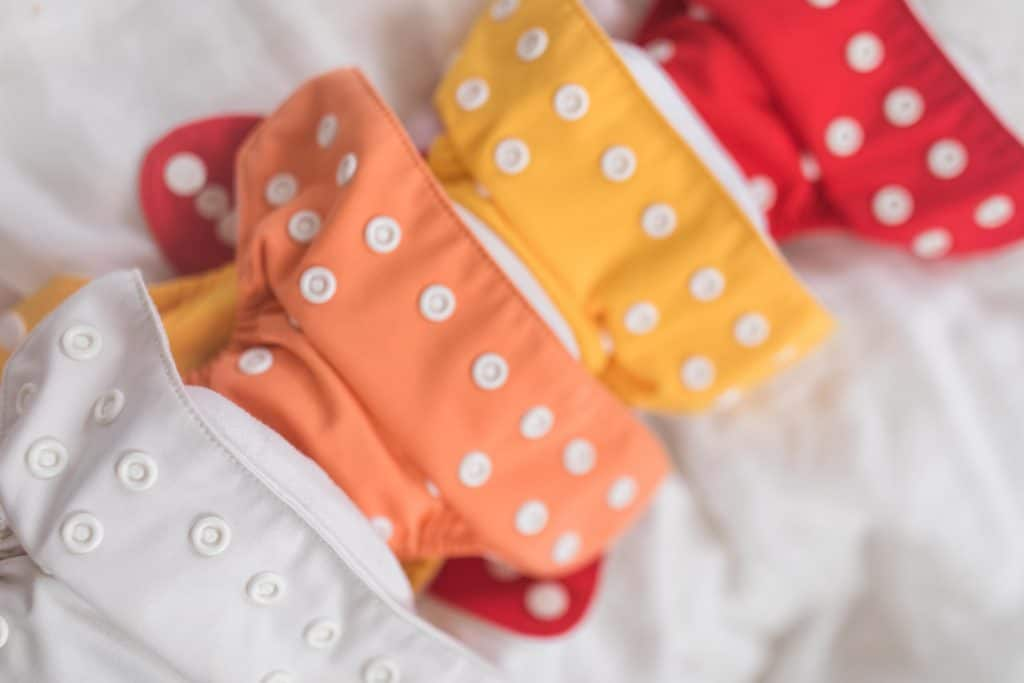 four newborn cloth diapers lined up in white, orange, yellow, and red