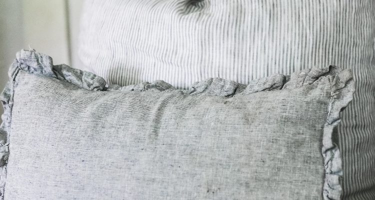 gray DIY ruffle pillow cover on a chair with a large pillow behind it.