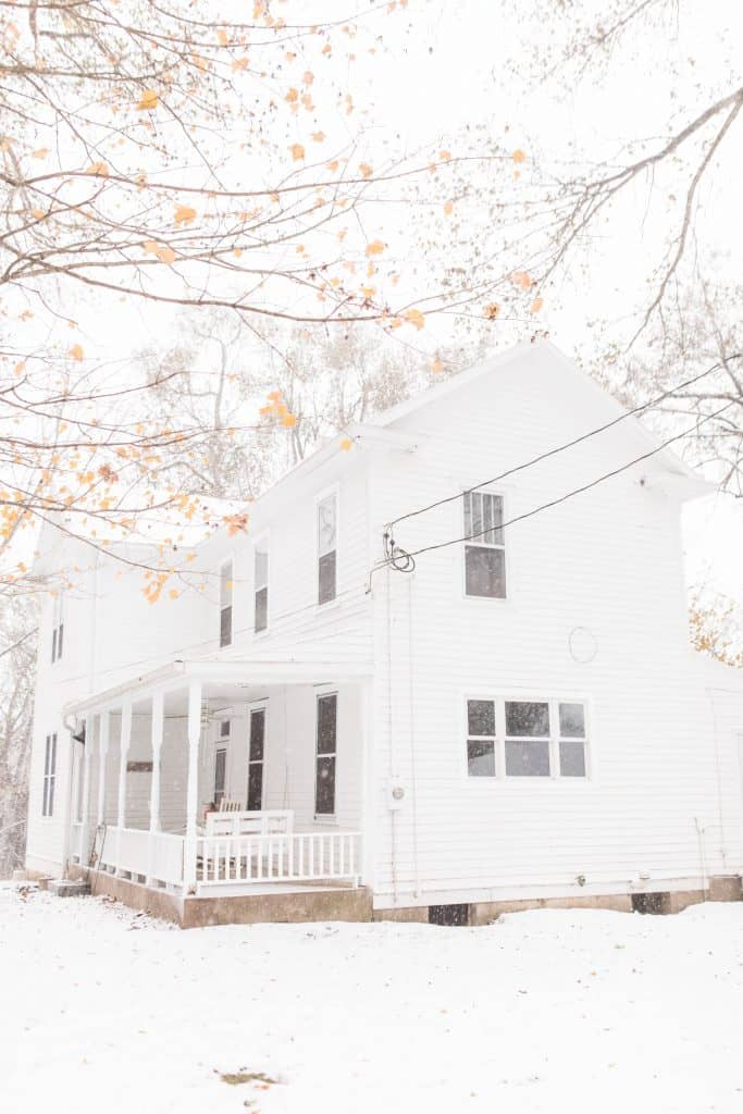 white victorian farmhouse in the snow