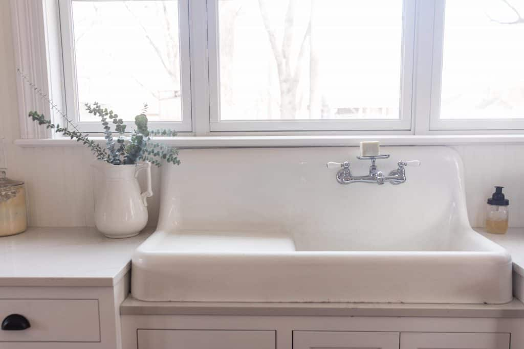 vintage white farmhouse apron sink with a beautiful chrome faucet. Fresh eucalyptus in a vintage iron stone vase to the right on quarts countertops