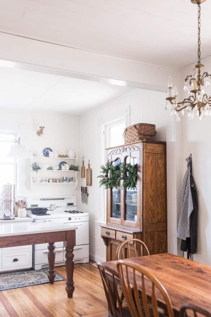 farmhouse kitchen table with antique brass chandelier. Victorian farmhouse kitchen in the background