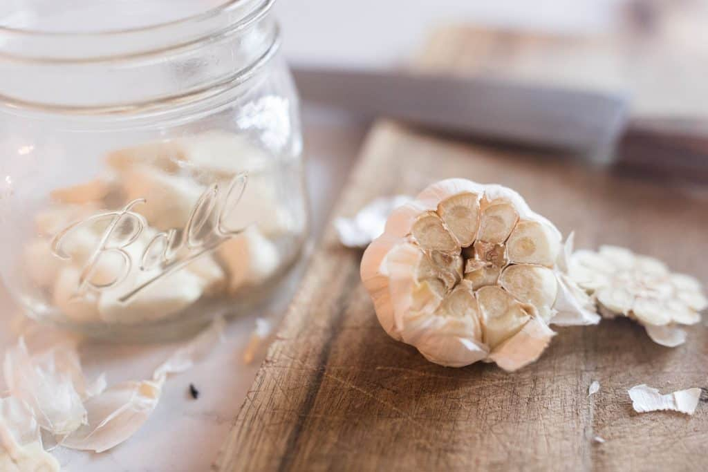 head of garlic with the top cut off with a jar of peeled garlic cloves in a jar to the left