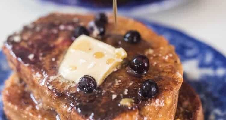 maple syrup being poured over sourdough French toast with blueberries on a blue plate with another plate of French toast in the background