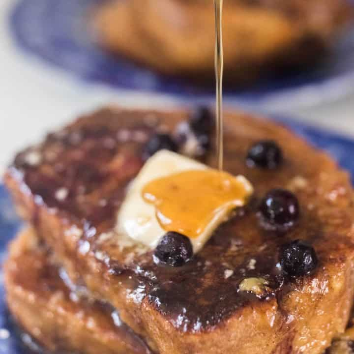 maple syrup being poured over sourdough French toast with blueberries